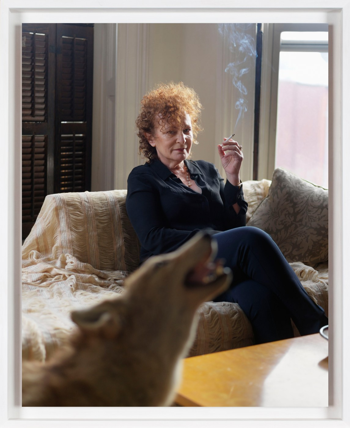 A color photograph of the artist Nan Goldin in her home. She is sitting on a chaise smoking a cigarette, and a barking dog is in the foreground.