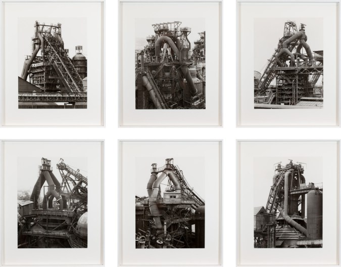 Grid of six framed black and white photographs of blast furnaces