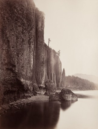 Ninteteenth century photograph of a sheer cliff side at the edge of a river