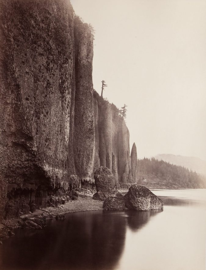 19th century photograph of a sheer cliff side at the edge of a river