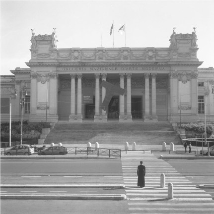 Black and white photograph of a person standing on an empty street in front of an art museum