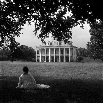 Black and white photograph of a woman sitting under a tree on a lawn looking at a large colonial-style house