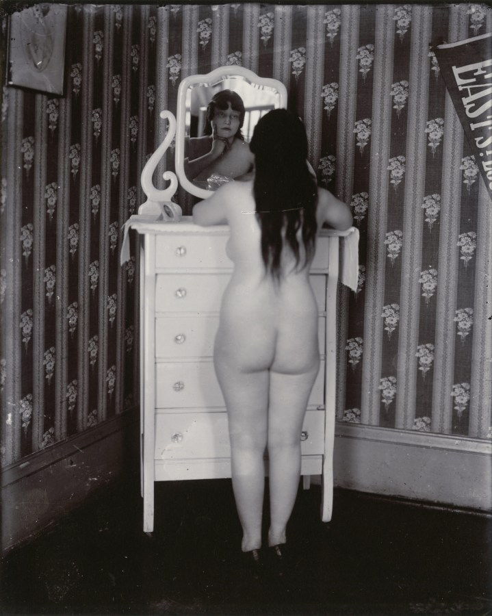 Black and white photograph of a nude woman standing at a dresser, facing away from the camera and reflected in the dresser mirror.