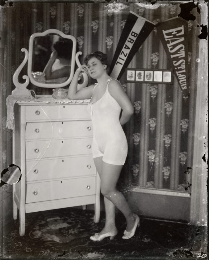 Black and white photograph of a woman in a negligee, leaning with her arm resting on a dresser