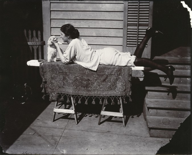 Black and white photograph of a woman laying on an ironing board, petting a small dog
