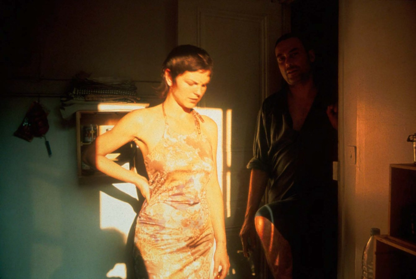 Color photograph inside a rom of a woman with her hand on her hip standing in the sunlight cast from a window and a man smoking a cigarette in a doorway behind her.