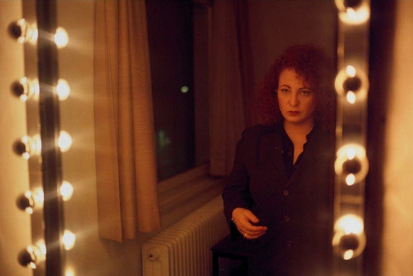 Color photograph of a mirror with circular lights on the sides, reflecting a woman standing, gazing into the mirror
