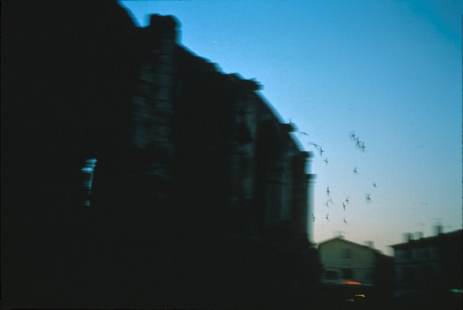 Blurred color photograph of a silhouetted building at dusk with birds flying by