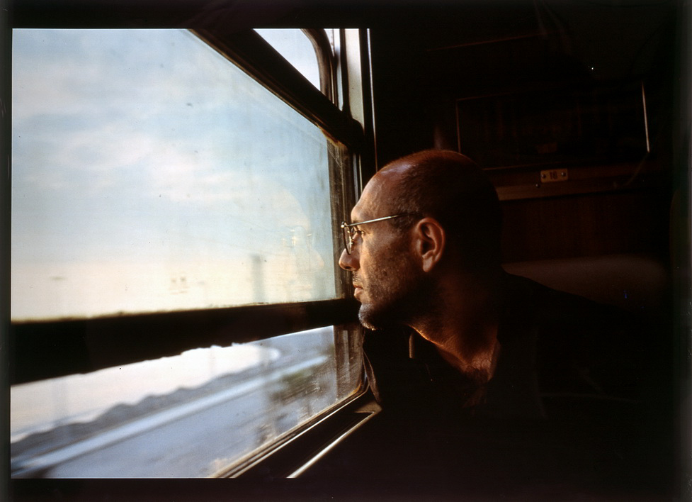 Color photograph of a man looking out a train window