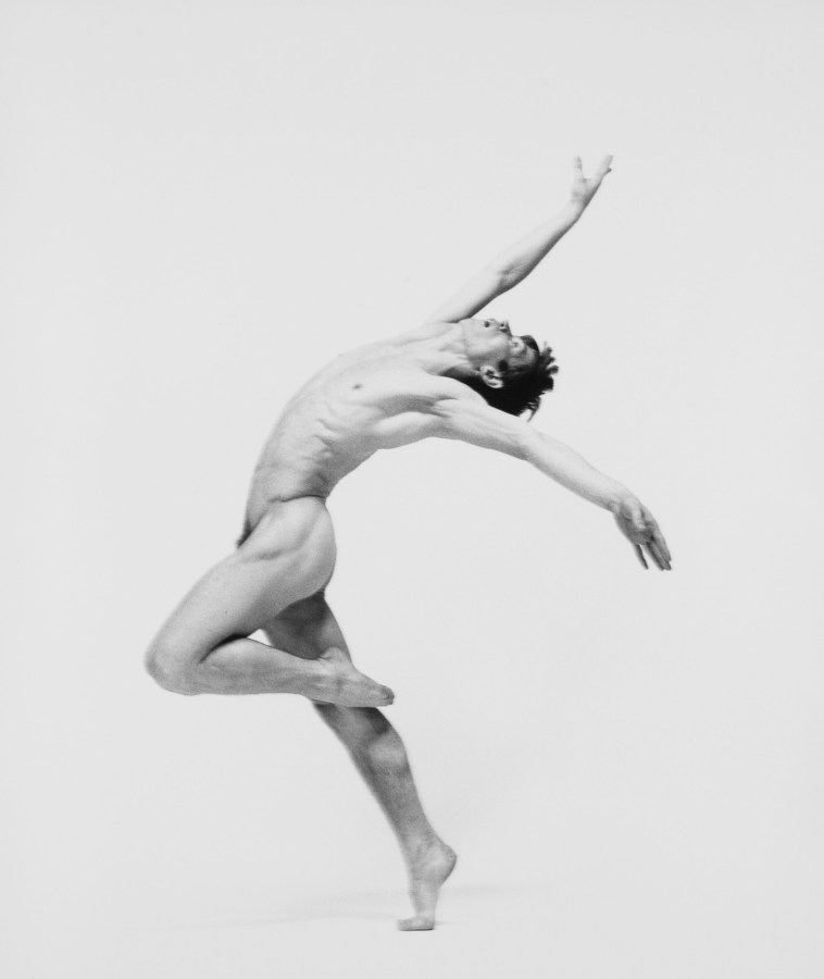 Black-and-white photograph of nude man dancing against white background