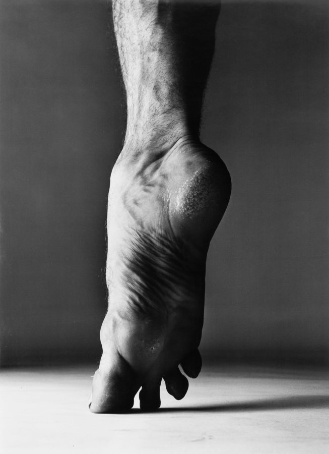 black-and-white photograph of a bare foot standing on tiptoe