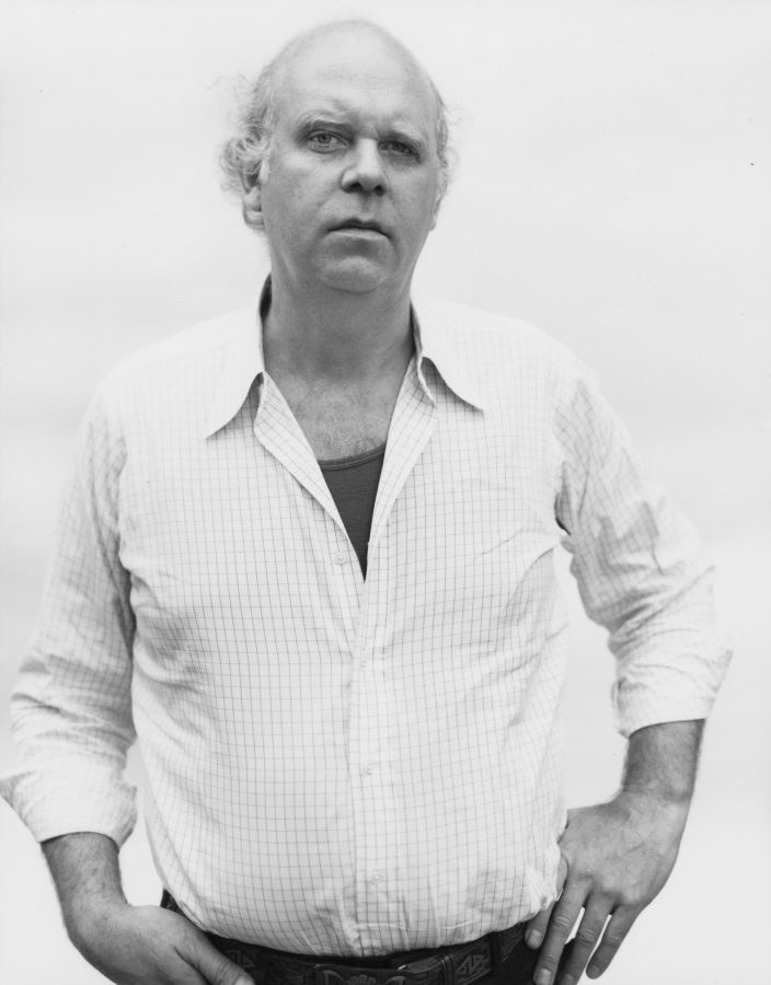 black and white photograph of a man looking directly at camera against a white background