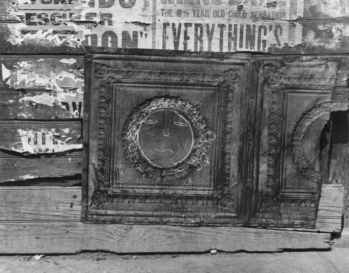 Black-and-white photograph of a wall with torn advertisements, and a moulded tin panel with a chalk drawing of a face.