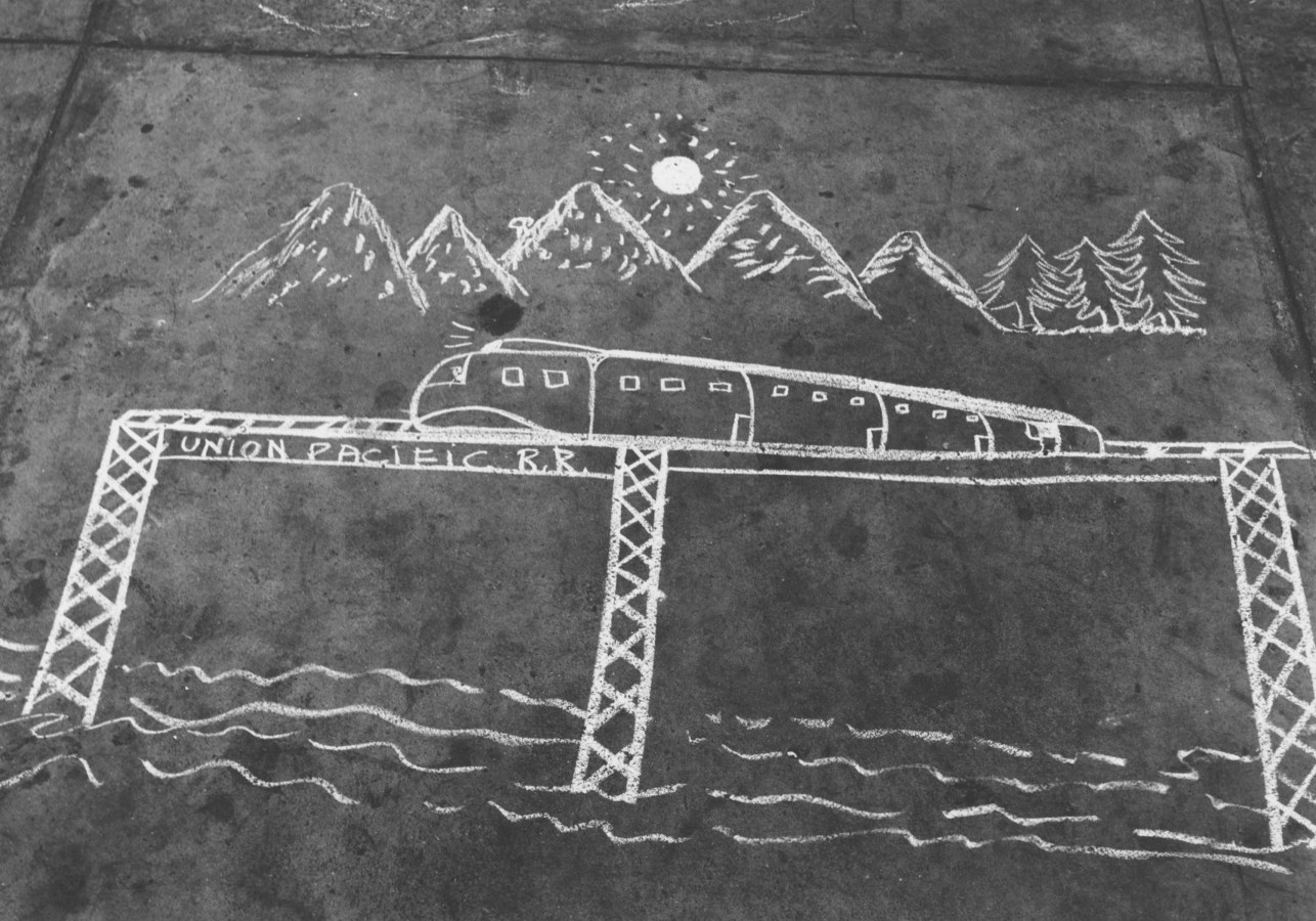 Black-and-white photograph depicting a sidewalk chalk drawing of a train on an elevated bridge, mountains, trees, and sun.