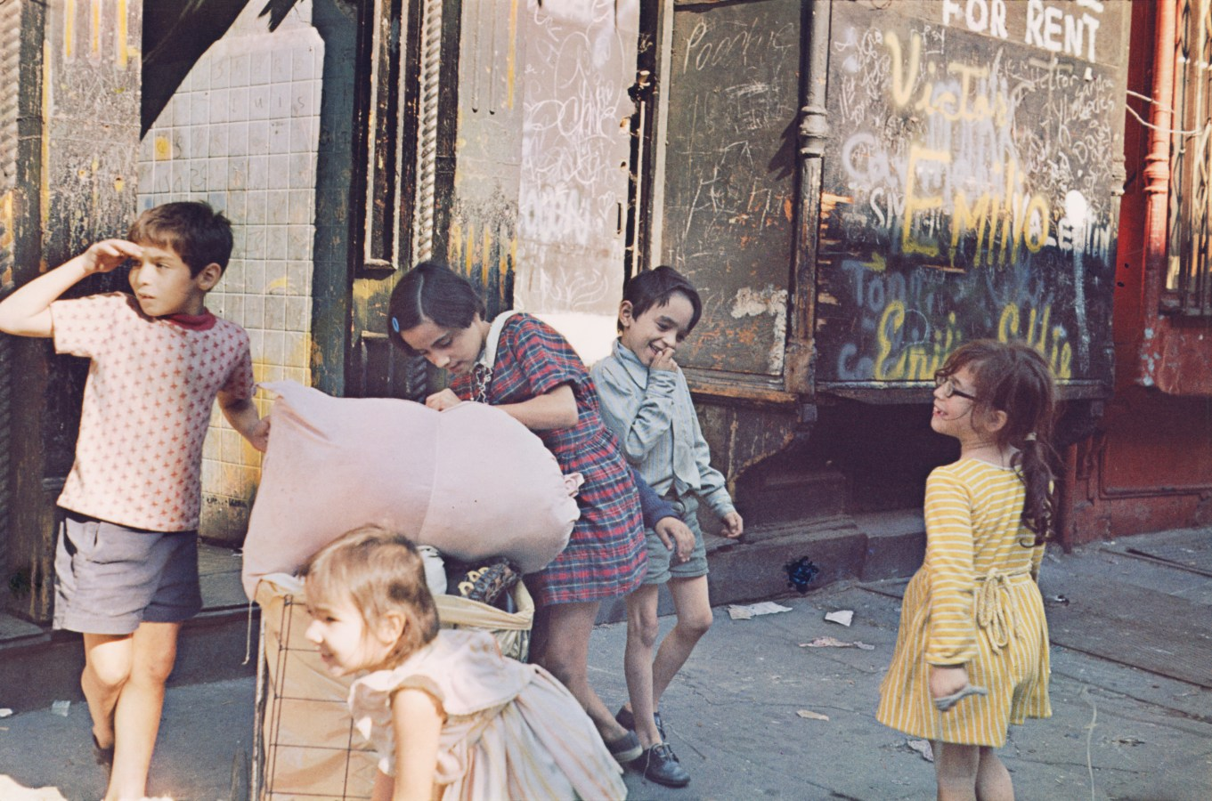 Color photograph of five children playing on the sidewalk.