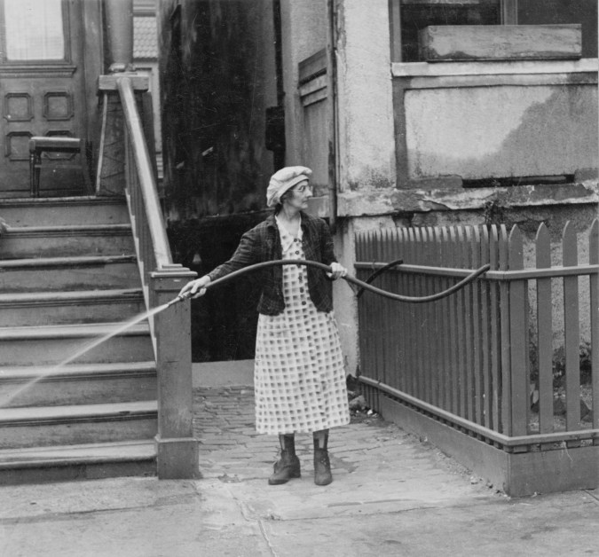 Black-and-white photograph of a woman in front of a brownstone, holding a watering hose.