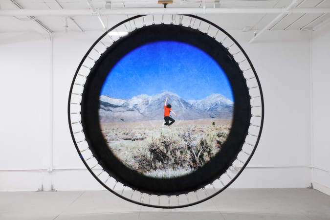 Trampoline hanging from a gallery ceiling with the image of a person jumping in a landscape projected onto it