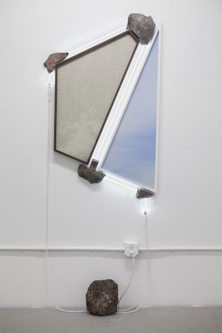 Two irregularly shaped framed prints of blank sky supported by stones and bordered by white neon lights