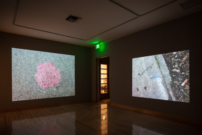 An installation shot of two projections in the darkened gallery