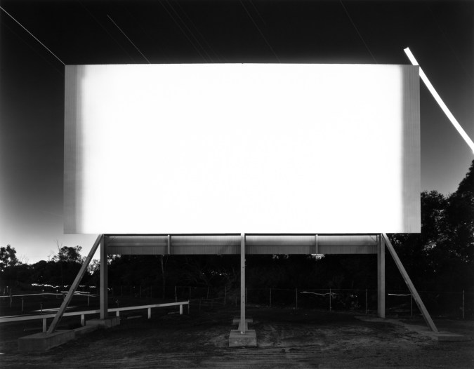A black and white photograph of a bright white movie screen at a drive-in theater at night, with bright star trails behind it