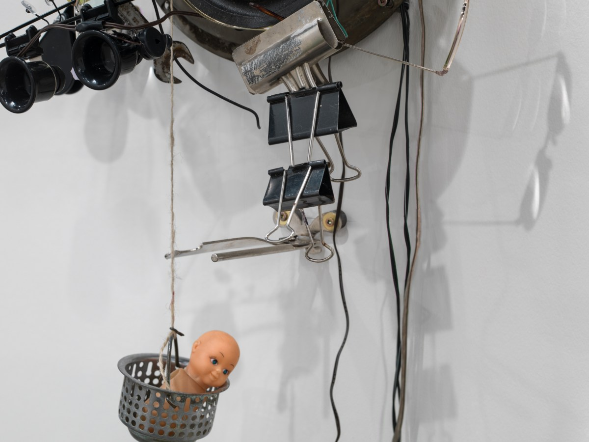 Close-up installation view of a mixed-media sculpture, showing binder clips and a small toy.