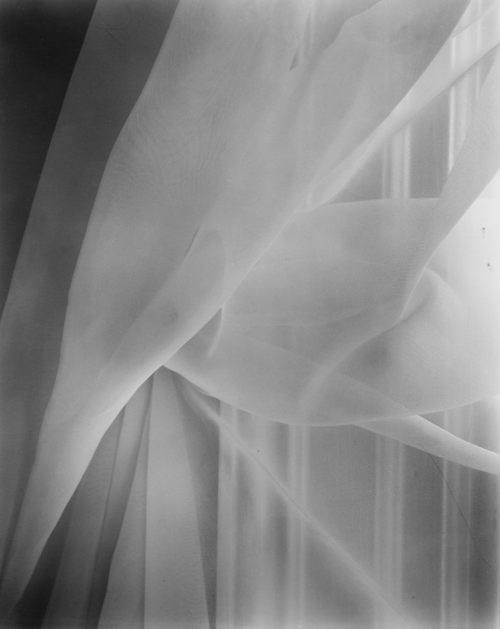Black-and-white photograph of a window curtain pulled back onto a hook in the window frame
