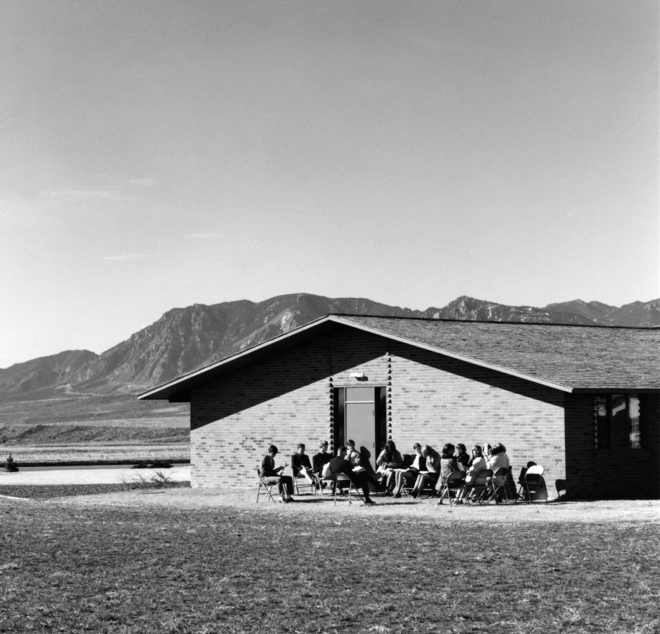 Black-and-white photograph of a group of people seated outside a modest building.