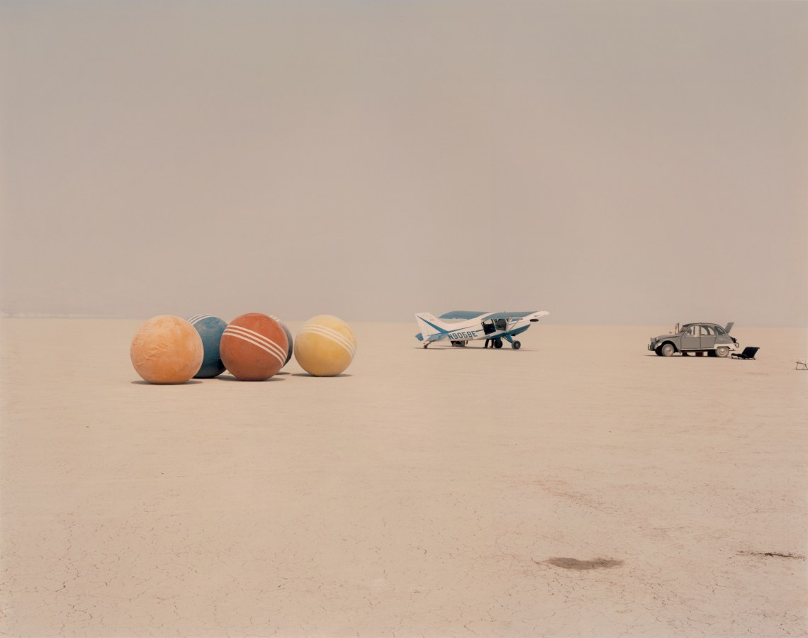 Color photograph of a desert field with a car and small aircraft, and four oversized croquet balls.