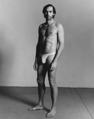 Black-and-white vertical photograph of a standing man wearing a jock strap.
