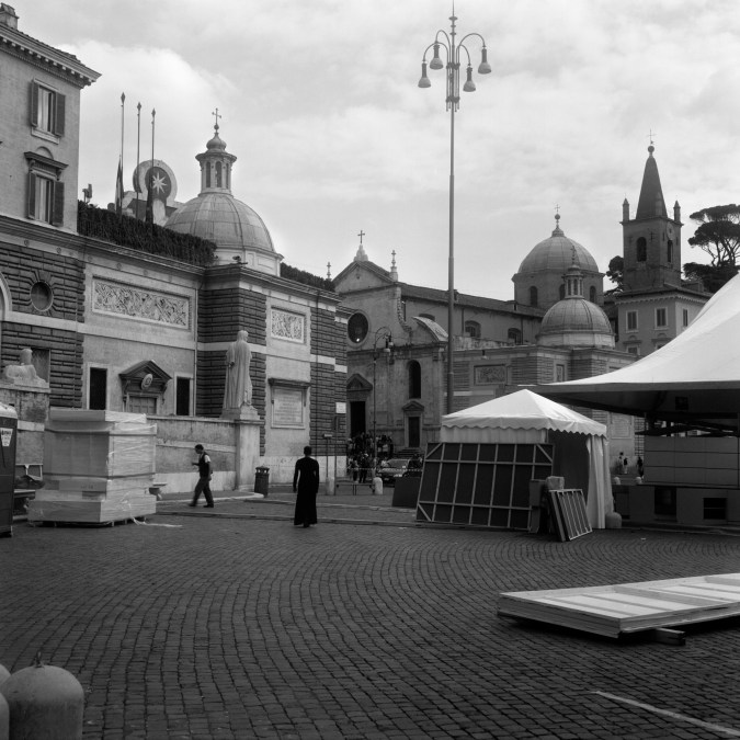 Black and white photograph of a solitary black-clad figure walking through a Roman plaza.