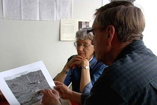Video still of two people examining a black and white print