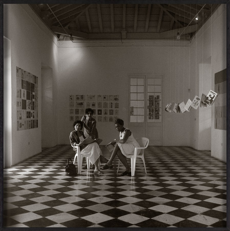 Framed black and white photograph of three people sitting in an art gallery