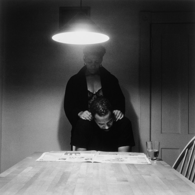 Black and white photograph of an African American couple at a kitchen table, a man seated and reading the paper, a woman standing behind with her hands on his shoulders.