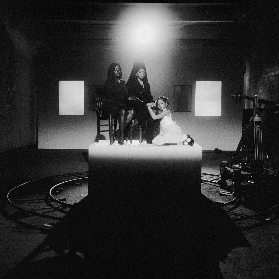Black and white photograph of three people seated on a pedestal lit by a spotlight in a darkened room