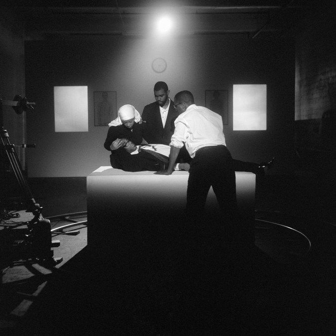 Black and white photograph showing a studio set upon which one female and two male African American figures are gathered around a supine African American man.