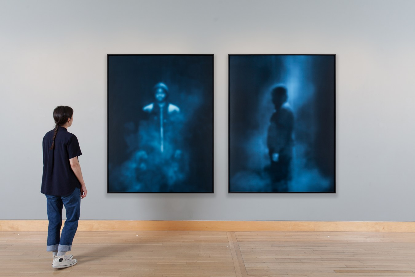 Installation view of a woman looking at a diptych of framed photographs.