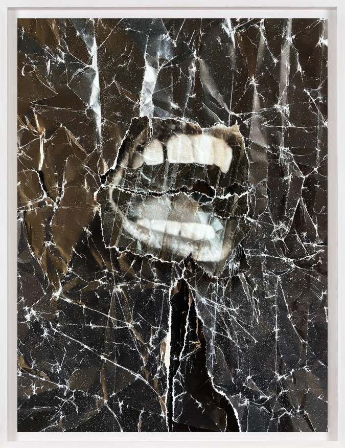 A framed collage of a crumpled black sheet, with a black and white image of a screaming mouth in the center.