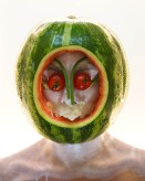 Color photograph of a person with a watermelon over their head.
