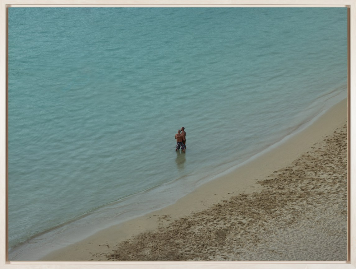 Framed color photograph of two men embracing as they stand at the edge of the ocean, looking toward the horizon.