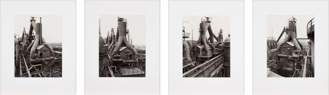 Four framed black and white photographs showing a factory building from various angles.