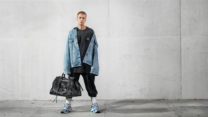Color photograph of Justin Bieber wearing Balenciaga standing against a start concrete wall.