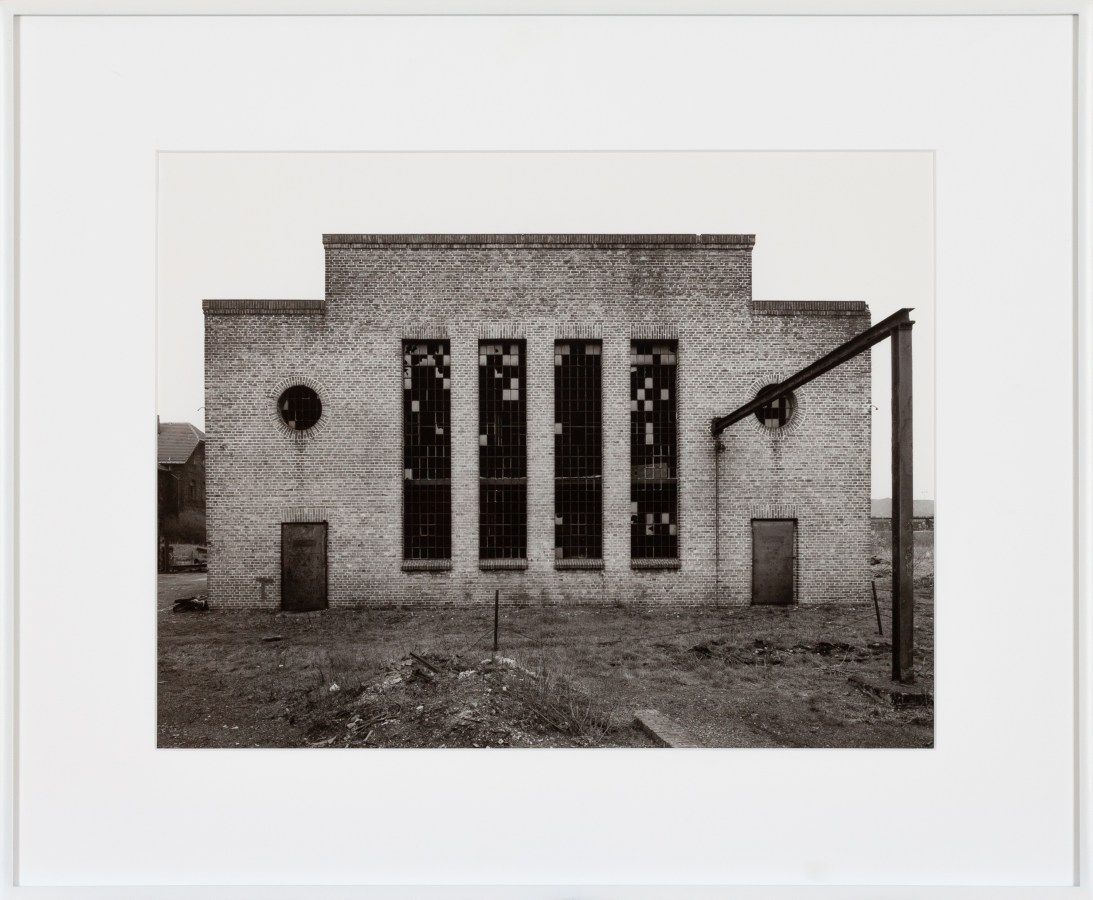 Framed black-and-white photograph showing the front of an industrial building.