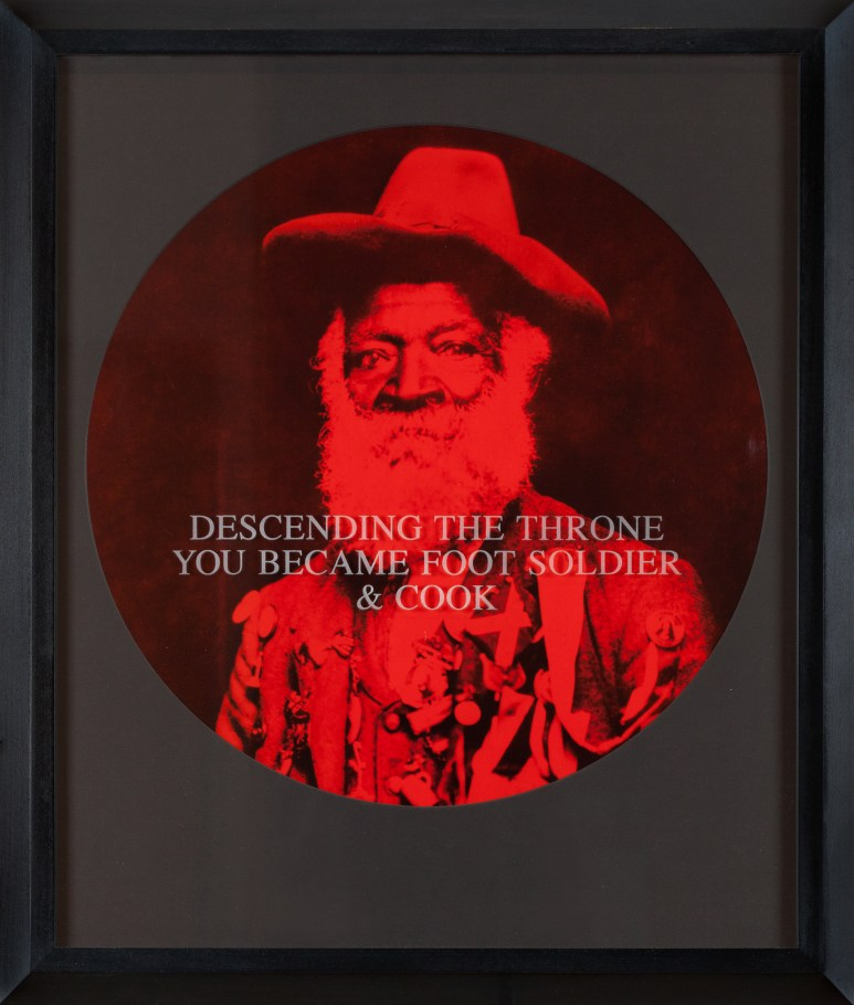 """A circular photograph printed in red and black tones depicts a bearded man staring into the camera, framed in a black frame. Text printed across the image reads """"Descending the Throne You Became Foot Soldier & Cook"""""""