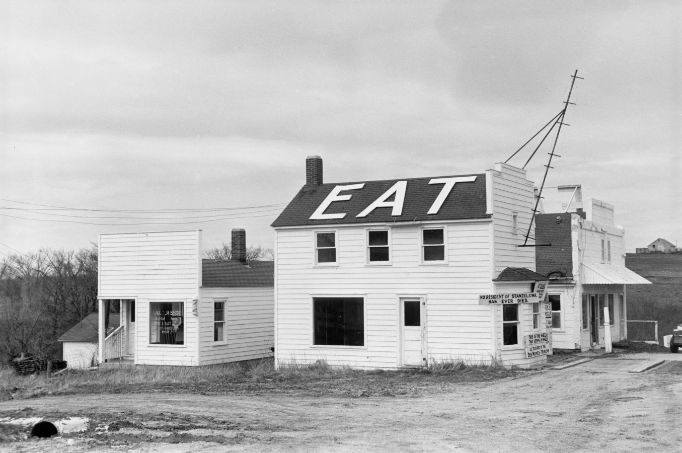 Black-and-white photograph of a rural two story building with the word 'eat' in large white letters on its roof.