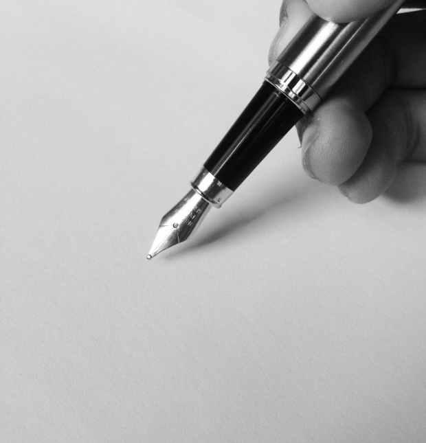 person holding fountain pen