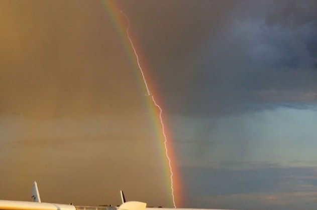 Lightning Hitting Plane Along The Path Of A Rainbow
