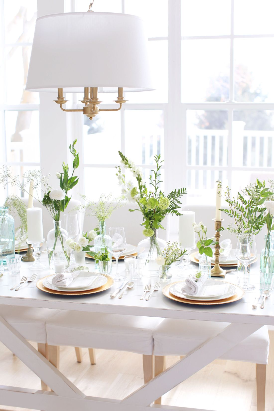 St. Patrick's Day Table Setting inspiration with gold chargers, greenery, green glass and white linens - that is also perfect for a light green and white wedding or dinner party.