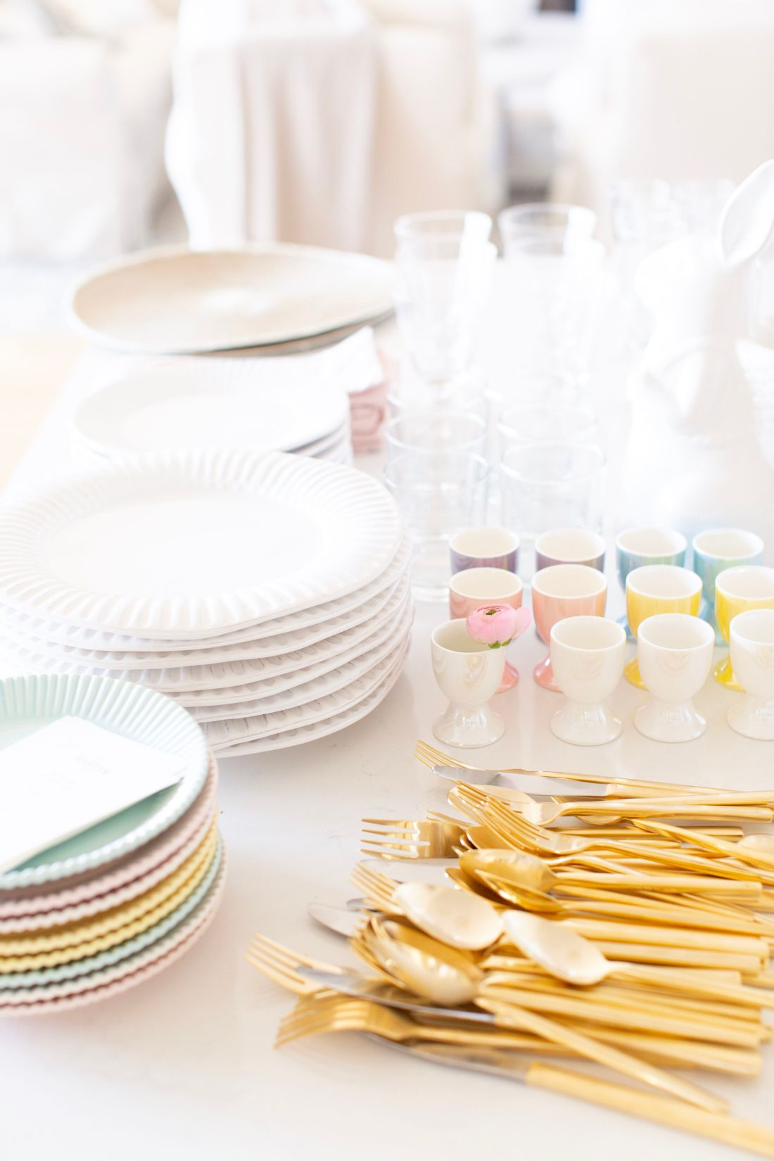Easter dinner preparation with pastel egg cups and gold flatware