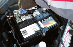 Engine bay showing 12V car battery and potential short circuit with metal battery bracket using wrench