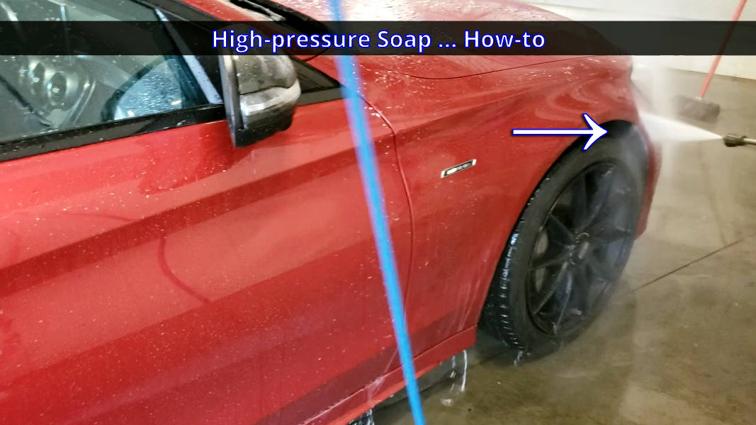 Using spray wand to wash between the bumper cover and front fender of the car